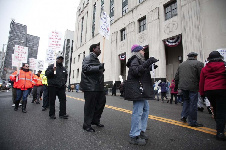 People protest outside the U.S. Courthouse where federal bankruptcy Judge Steven Rhodes is overseeing Detroit's bankruptcy. Rhodes last week scheduled a hearing for Monday, December 16, in order to hear appeals in the case. (File photo by Bill Pugliano/Getty Images)