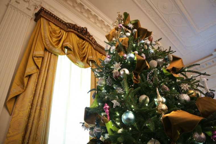 A Christmas tree stands next to a window in the East Room of the White House December 4, 2013 in Washington, DC. U.S. first lady Michelle Obama will host today military families for the first viewing of the 2013 holiday decorations and demonstrating holiday crafts and treats to military children. (Alex Wong/Getty Images)