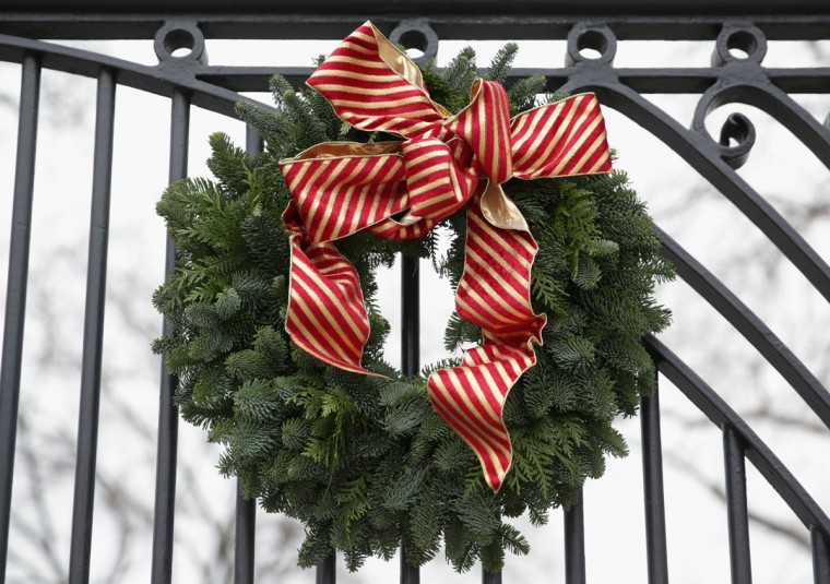 A Christmas wreath is hung on a gate of the White House December 4, 2013 in Washington, DC. U.S. first lady Michelle Obama will host today military families for the first viewing of the 2013 holiday decorations and demonstrating holiday crafts and treats to military children. (Alex Wong/Getty Images)