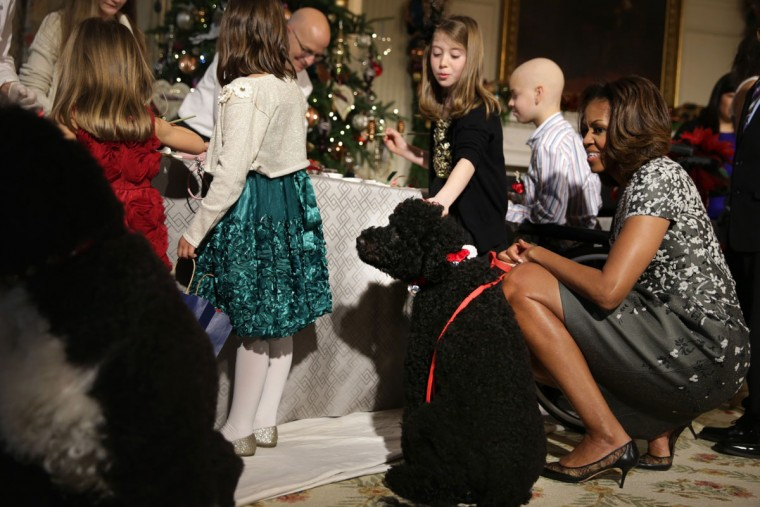 U.S. first lady Michelle Obama (R) greets military children with her dog Sunny at the State Dining Room of the White House during an event to preview the 2013 holiday decorations December 4, 2013 in Washington, DC. The first lady hosted military families for the first viewing of the decorations and demonstrating holiday crafts and treats to military children. (Alex Wong/Getty Images)