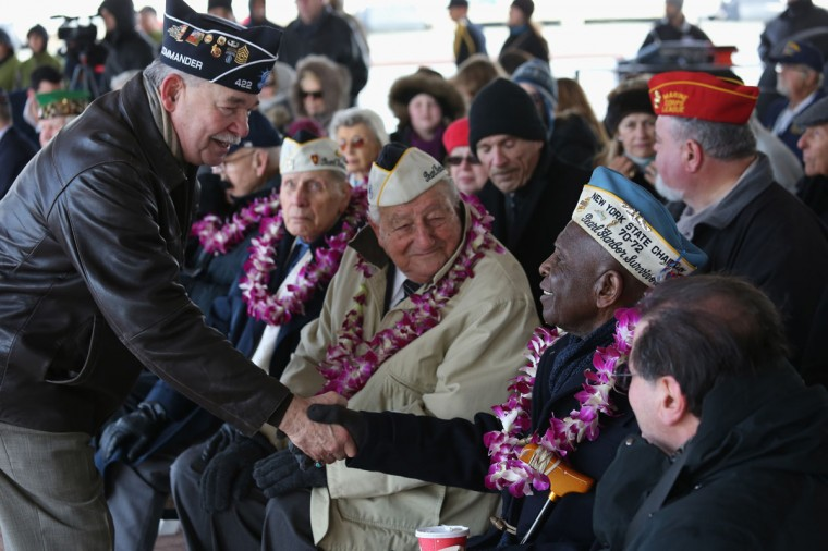 Pearl Harbor survivor Clark Simmons, 92, is congratulated after he spoke at a ceremony marking the 72nd anniversary of the attack on Pearl Harbor, Hawaii on December 7, 2013 in New York City. Four Pearl Harbor survivors from the New York area gathered with former crew members of the USS Intrepid to mark the Japanese surprise attack on December 7, 1941 which killed 2,402 Americans and brought the United States into WWII. (John Moore/Getty Images)