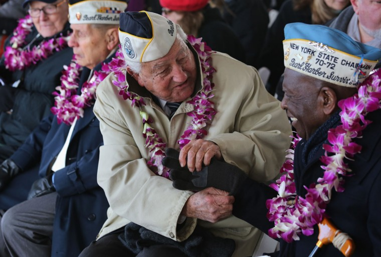 Pearl Harbor survivor Armando Galella, 92, helps fellow survivor Clark Simmons, 92, with his gloves at a ceremony marking the 72nd anniversary of the attack on Pearl Harbor, Hawaii on December 7, 2013 in New York City. Four Pearl Harbor survivors from the New York area gathered with former crew members of the USS Intrepid to mark the Japanese surprise attack on December 7, 1941 which killed 2,402 Americans and brought the United States into WWII. (John Moore/Getty Images)