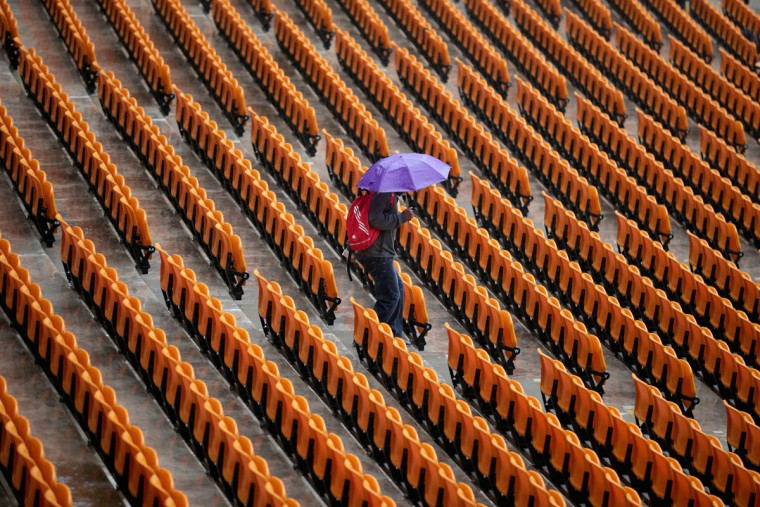 An early arrival looks for a place to sit out of the rain in the 95,000-seat FNB Stadium before the start of the official memorial service for former South African President Nelson Mandela December 10, 2013 in Johannesburg, South Africa. Over 60 heads of state have traveled to South Africa to attend a week of events commemorating the life of former South African President Nelson Mandela. (Chip Somodevilla/Getty Images)