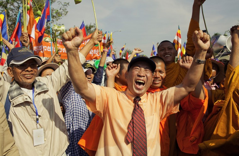 Mam Sonando, a former Amnesty International prisoner of conscience, celebrates his arrival at the Cambodian National Assembly following an extended 10 day march on December 10, 2013 in Phnom Penh, Cambodia. Various groups of activists, political parties, monks and humanitarian organizations are holding events for International Human Rights Day in the Cambodian capital. Six groups of monks and activists have walked from different parts of the country to deliver petitions collected en route, detailing human rights abuse cases. (Omar Havana/Getty Images)