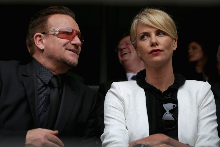 Singer Bono and South African actor Charlize Theron arrive for the official memorial service for former South African President Nelson Mandela at FNB Stadium December 10, 2013 in Johannesburg, South Africa. Over 60 heads of state have traveled to South Africa to attend a week of events commemorating the life of former South African President Nelson Mandela. (Chip Somodevilla/Getty Images)