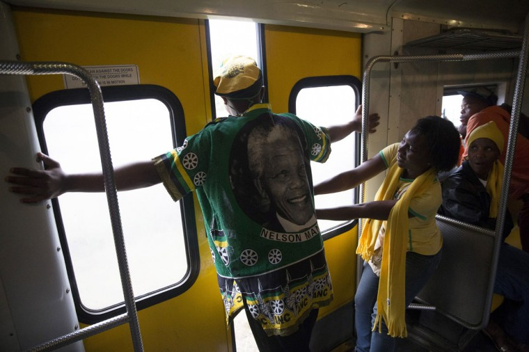 A passenger pries open the doors of a moving train carrying people to the Nelson Mandela memorial service to gain a view of the FNB Stadium, on December 10, 2013 in Johannesburg, South Africa. Over 60 heads of state have traveled to South Africa to attend a week of events commemorating the life of former South African President Nelson Mandela. (Oli Scarff/Getty Images)