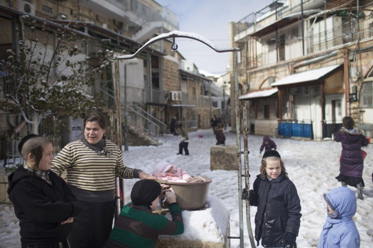 Ultra-orthodox Jews enjoy the snow in the Mea Shearim religious neighborhood on December 12, 2013 in Jerusalem's old city, Israel. (Photo by Uriel Sinai/Getty Images)