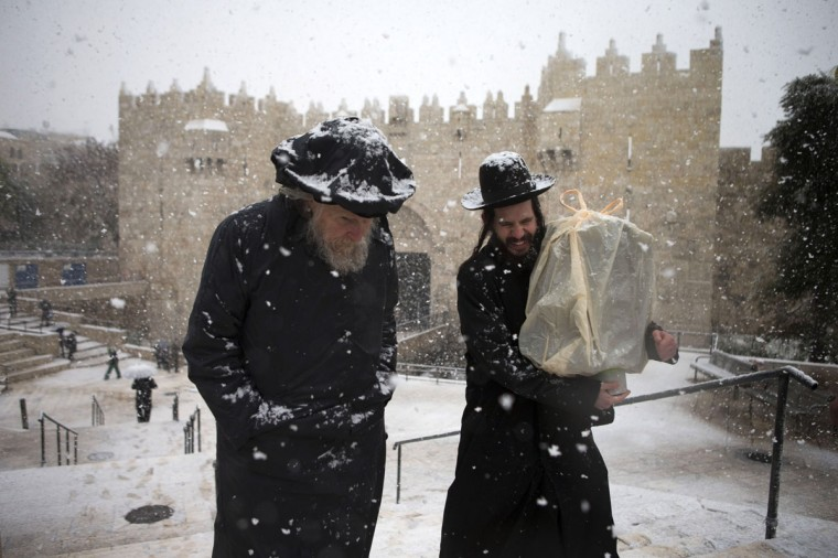Orthodox Jews walk past the Damascus gate on December 12, 2013 outside Jerusalem's old city, Israel. (Photo by Uriel Sinai/Getty Images)