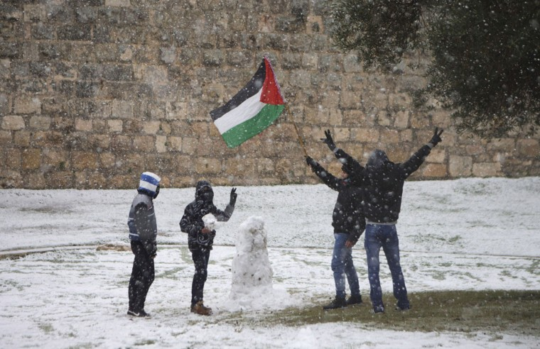 Palestinian play and wave the Palestinian flag in the snow near the Damascus gate on December 12, 2013 outside Jerusalem's old city, Israel. A heavy winter storm hit much of the Middle East yesterday evening into today, forcing the closure of roads and schools while covering widespread areas with snow and ice. (Uriel Sinai/Getty Images)