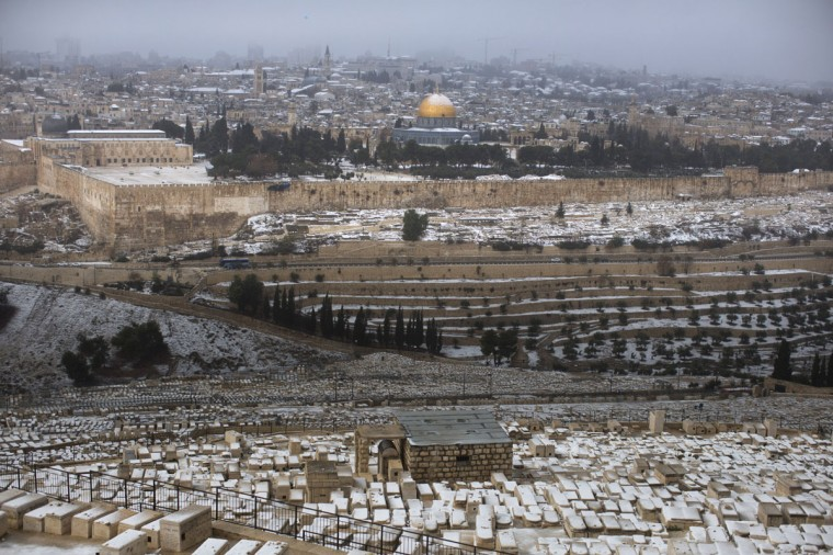 An Israeli man throws a snowball as snow covers the Dome of the Rock at the Al-Aqsa mosque compound in the backround on December 12, 2013 in Jerusalem, Israel. (Photo by Uriel Sinai/Getty Images)