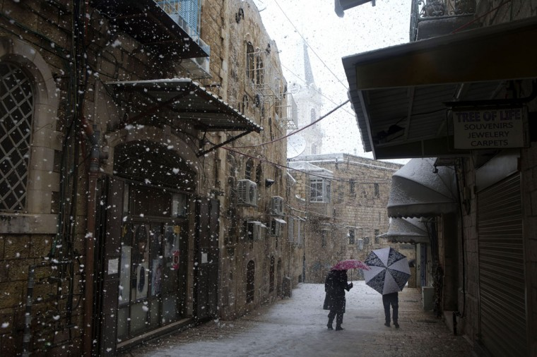 Israelis walk in the snow on December 12, 2013 in Jerusalem's old city, Israel. A heavy winter storm hit much of the Middle East, forcing the closure of roads and schools while covering widespread areas with snow and ice. (Photo by Uriel Sinai/Getty Images)