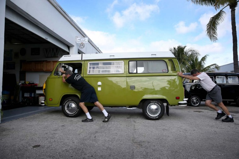 "Bruce Wolczanski (L) and Don Ammann push a 1976 Volkswagen camper bus into a garage bay for repair at their McNab Foreign Car garage which specializes in restoring VW vehicles on December 12, 2013 in Pompano Beach, Florida. After 64 years, the German automaker announced it will finally stop producing the bus on December 20 in Brazil, the last country in the world to manufacture the van. Mr. Wolczanski said, 'he feels bad that the car will no longer be made, but it will live on as people drag them out of barns, fields and backyards and restore them'. He sees the buses continue to have a cult following with more and more young people buying and restoring the buses, ""they will never die"". (Photo by Joe Raedle/Getty Images)"