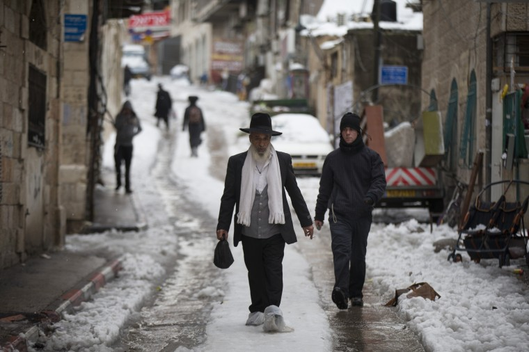 An Ultra Orthodox Jewish man walks in the snow a head of Shabat (Saturday), At the Mea Shearim Ultra orthodox jewish neighborhood on December 13, 2013 in Jerusalem, Israel. Heavy storms continued throughout Israel on Friday, causing traffic disruptions and power outages across the country. (Uriel Sinai/Getty Images)