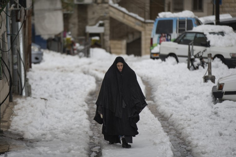 An Ultra orthodox Jewish woman walks in the snow a head of Shabat (Saturday), At the Mea Shearim Ultra orthodox jewish neighborhood on December 13, 2013 in Jerusalem, Israel. Heavy storms continued throughout Israel on Friday, causing traffic disruptions and power outages across the country. (Uriel Sinai/Getty Images)