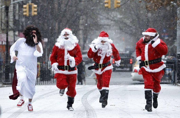 """Revelers dressed as Santa Claus run as the arrive at Tompkins Square Park to take part during the annual SantaCon bar crawl event on December 14, 2013 in New York City. The SantaCon annual event occurs worldwide in more than 300 cities in 44 countries. In New York some community groups have established a """"Santa Free"""" zone that urges bars not to serve alcoholic beverages to people participating in order to dissuade incidents of public vomiting and urination in the streets. (Kena Betancur/Getty Images)"""