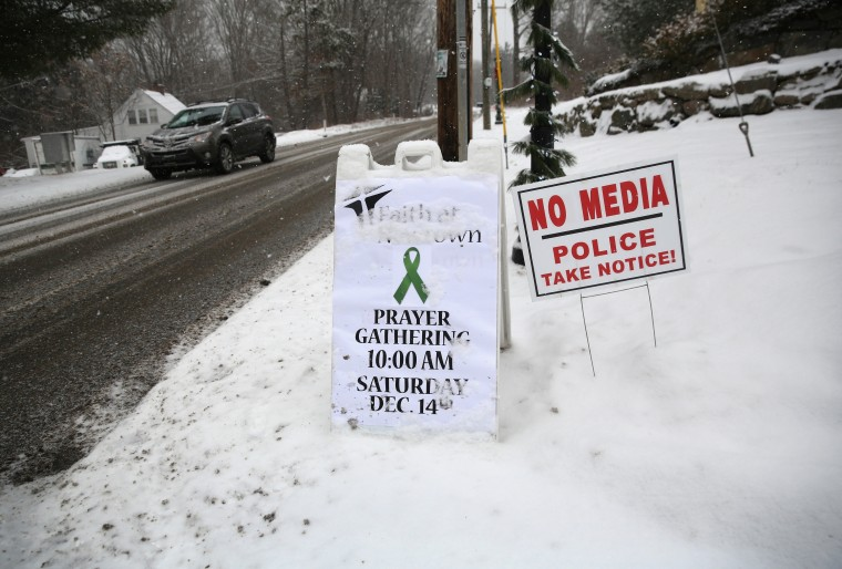 Signs stand in front of a church near the former site of Sandy Hook Elementary on December 14, 2012 in Newtown, Connecticut. One year ago Adam Lanza shot and killed 20 first graders and six adults at the school. Newtown decided not to hold a public memorial on the anniversary out of respect for victims' survivors, and the town appealed for privacy. (John Moore/Getty Images)