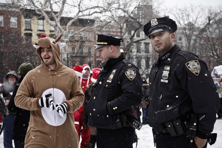 Members of the New York Police Department stand next to revelers dressed as Santa Claus and holiday costumes as they gather at Tompkins Square Park during the annual SantaCon bar crawl event on December 14, 2013 in New York City. The SantaCon annual event occurs worldwide in more than 300 cities in 44 countries. In New York some community groups have established a 'Santa Free' zone that urges bars not to serve alcoholic beverages to people participating in order to dissuade incidents of public vomiting and urination in the streets. (Kena Betancur/Getty Images)