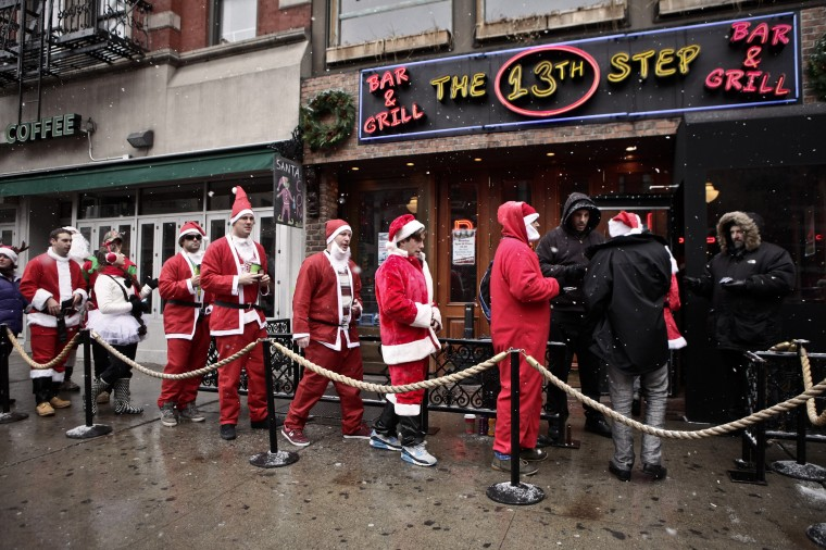 Revelers dressed as Santa Claus line up outside a bar in the East Village neighborhood during the annual SantaCon bar crawl event on December 14, 2013 in New York City. The SantaCon annual event occurs worldwide in more than 300 cities in 44 countries. In New York some community groups have established a 'Santa Free' zone that urges bars not to serve alcoholic beverages to people participating in order to dissuade incidents of public vomiting and urination in the streets. (Kena Betancur/Getty Images)