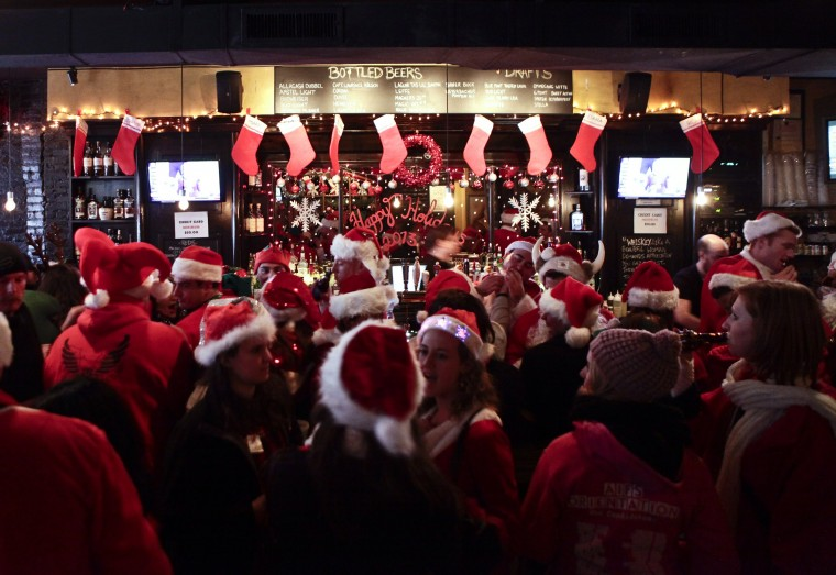 Revelers dressed as Santa Claus gather inside at a bar in the East Village neighborhood during the annual SantaCon bar crawl event on December 14, 2013 in New York City. The SantaCon annual event occurs worldwide in more than 300 cities in 44 countries. In New York some community groups have established a 'Santa Free' zone that urges bars not to serve alcoholic beverages to people participating in order to dissuade incidents of public vomiting and urination in the streets. (Kena Betancur/Getty Images)