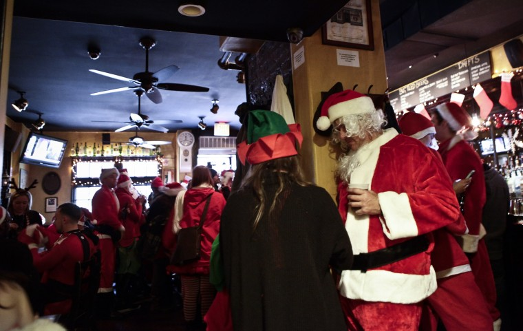 Revelers dressed as Santa Claus drink inside at a bar in the East Village neighborhood during the annual SantaCon bar crawl event on December 14, 2013 in New York City. The SantaCon annual event occurs worldwide in more than 300 cities in 44 countries. In New York some community groups have established a 'Santa Free' zone that urges bars not to serve alcoholic beverages to people participating in order to dissuade incidents of public vomiting and urination in the streets. (Kena Betancur/Getty Images)