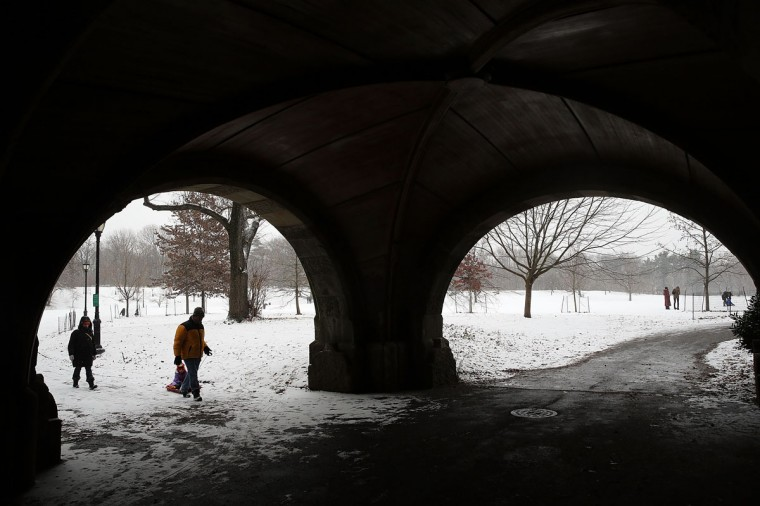 People walk through Prospect Park during a snow storm on December 14, 2013 in Brooklyn. (Spencer Platt/Getty Images)