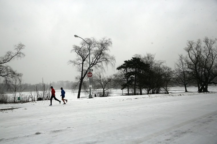 People run through Prospect Park during a snow storm on December 14, 2013 in Brooklyn. (Spencer Platt/Getty Images)