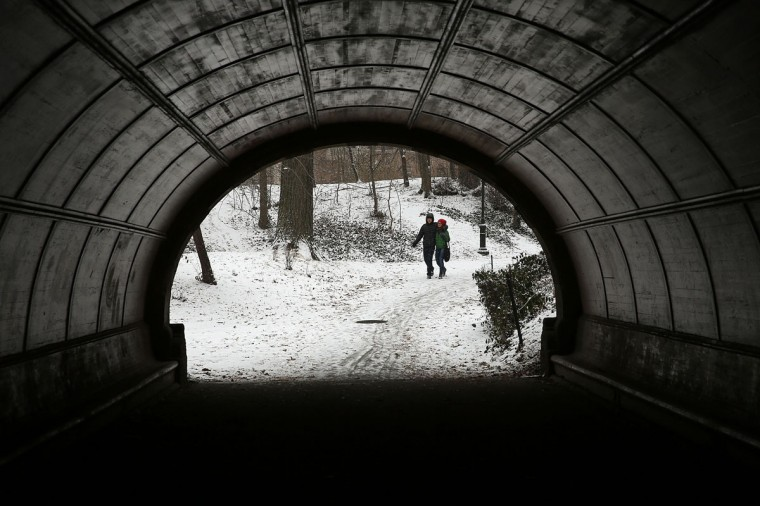 A couple walks through Prospect Park during a snow storm on December 14, 2013 in the Brooklyn borough of New York City. (Spencer Platt/Getty Images)