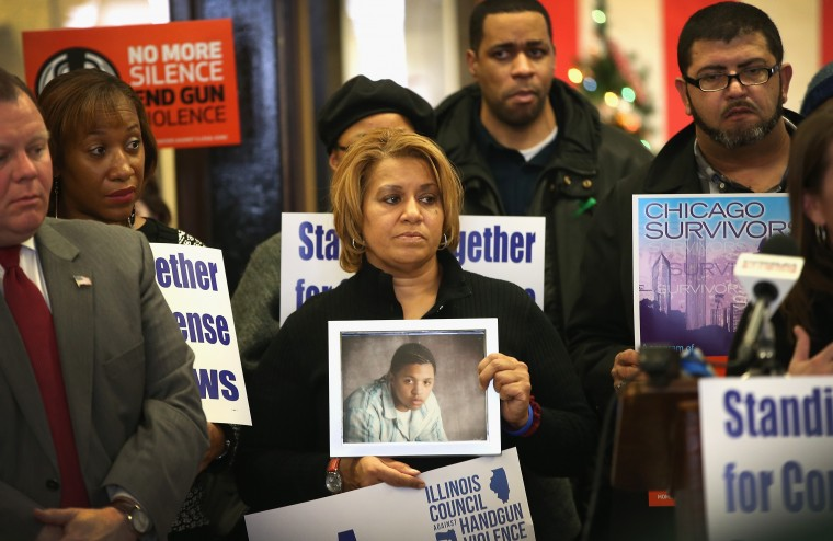 Annette Nance-Holt (C) holds a picture of her son Blair during a gathering of gun violence victims and gun control advocates at Cornell Square Park on the anniversary of the Sandy Hook Elementary School shooting December 14, 2013 in Chicago, Illinois. Thirteen people, including a three-year-old boy, were wounded when gunmen opened fire on a crowd gathered at the basketball courts in Cornell Square Park in September. Twenty children and 6 adults were killed when a gunman opened fire at Sandy Hook School. Blair, 16, was killed riding a bus on his way to help out at his grandparents store in May 2007. His teenaged killer was sentenced to 100 years in prison. Nearly 1000 people have been murdered in Chicago in the past two year, most by gunfire. (Scott Olson/Getty Images)