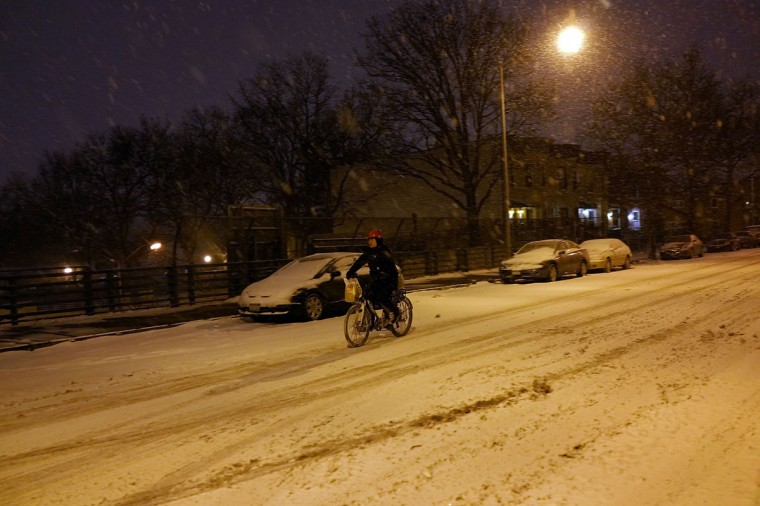 A person rides a bike during a snow storm on December 14, 2013 in the Brooklyn borough of New York. (Spencer Platt/Getty Images)