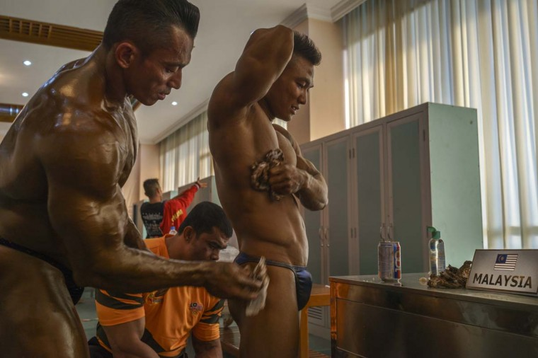 Hashrine Hashim of Malaysia helps team member Azuwan Jef get ready to compete in the bodybuilding contest at the Myanmar Convention Center during the 2013 SEA Game on December 14, 2013 in Yangon, Burma. (Ruben Salgado Escudero/Getty Images)