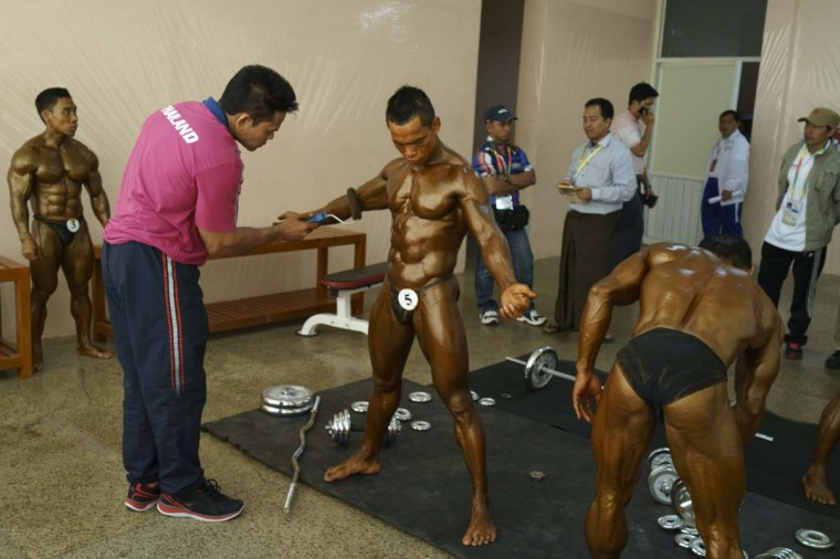 Phanorn Onnim of Thailand gets tanned up before competing in the bodybuilding contest at the Myanmar Convention Center during the 2013 SEA Game on December 14, 2013 in Yangon, Burma. (Ruben Salgado Escudero/Getty Images)