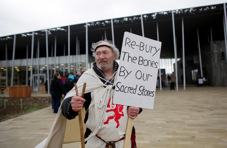 A Druid demonstrator stands in front of the new Stonehenge visitor centre in protest at the English Heritage display of ancient human remains excavated from the environs of Stonehenge on December 18, 2013 in Wiltshire, England. English Heritage unveiled the new multi-million pound visitor centre at Stonehenge - located about a mile-and-a-half (2km) from the stones - which also included grassing over the road alongside the ancient monument and closure of the existing 1960s facilities this week. Stonehenge, built between 3,000 BC and 1,600 BC, attracts around 900,000 visitors a year, with 70 percent of those from overseas. (Matt Cardy/Getty Images)