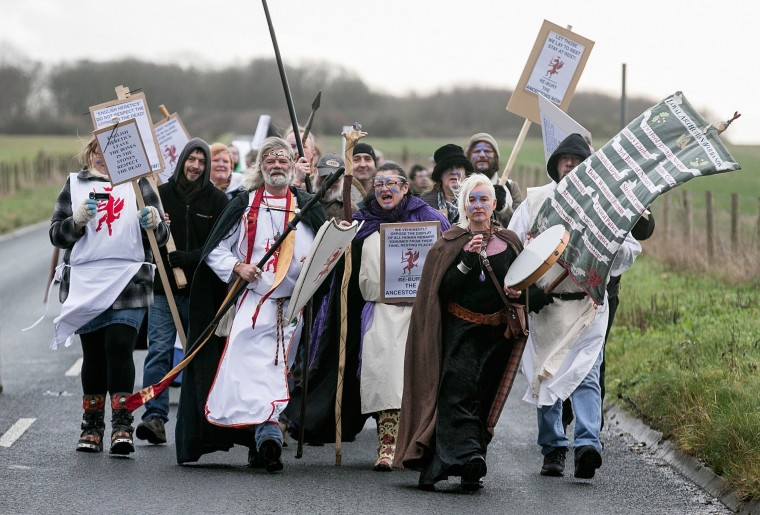King Arthur Pendragon, a senior Druid, leads a protest march past the new Stonehenge visitor centre in protest at English Heritage display of ancient human remains excavated from the environs of Stonehenge on December 18, 2013 in Wiltshire, England. English Heritage unveiled the new multi-million pound visitor centre at Stonehenge - located about a mile-and-a-half (2km) from the stones - which also included grassing over the road alongside the ancient monument and closure of the existing 1960s facilities this week. Stonehenge, built between 3,000 BC and 1,600 BC, attracts around 900,000 visitors a year, with 70 percent of those from overseas. (Matt Cardy/Getty Images)
