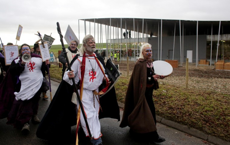 King Arthur Pendragon, a senior Druid, (C) leads a protest march past the new Stonehenge visitor centre in protest at English Heritage display of ancient human remains excavated from the environs of Stonehenge on December 18, 2013 in Wiltshire, England. English Heritage unveiled the new multi-million pound visitor centre at Stonehenge - located about a mile-and-a-half (2km) from the stones - which also included grassing over the road alongside the ancient monument and closure of the existing 1960s facilities this week. Stonehenge, built between 3,000 BC and 1,600 BC, attracts around 900,000 visitors a year, with 70 percent of those from overseas. (Matt Cardy/Getty Images)