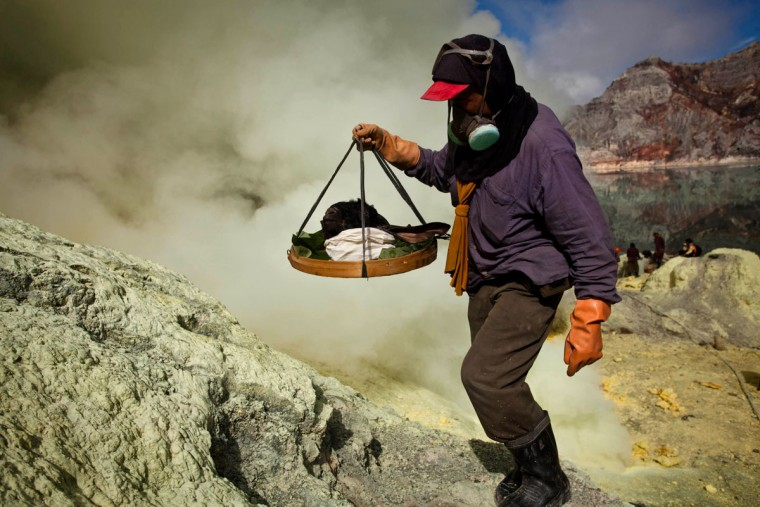 A miner carry a goats head for burial in the crater as part of an annual offering ceremony on the Ijen volcano on December 17, 2013 in Yogyakarta, Indonesia. The ritual is performed by the sulfur miners of Mount Ijen who slaughter a goat and then bury the head in the crater of mount Ijenn. The sacrifice is performed to ward off potential disasters for the next year. The Ijen crater rises to 2,386m, with a depth of over 175m, making it one of the world's largest craters. Sulfur mining is a major industry in the region, made possible by an active vent at the edge of a lake, but the work is not without risks as the acidity of the water in the crater is high enough to dissolve clothing and cause breathing problems. (Ulet Ifansasti/Getty Images)