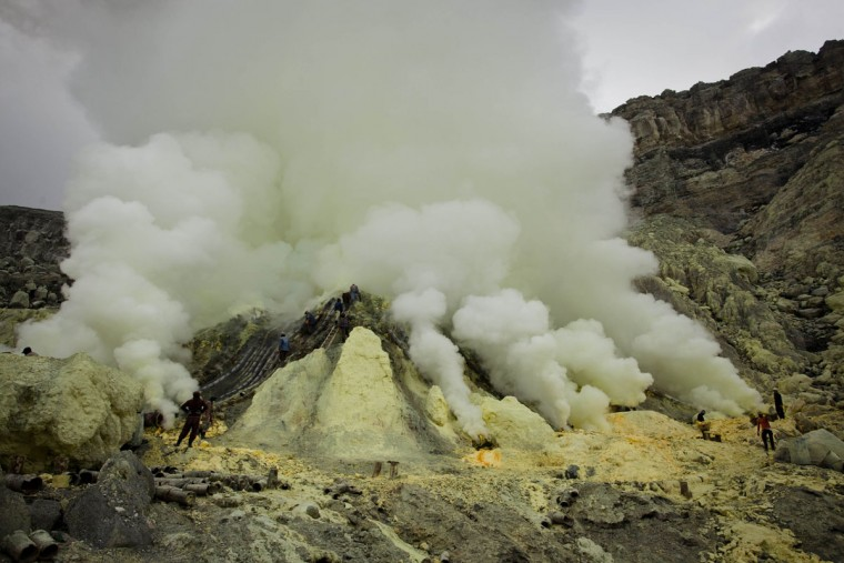Miners extracts sulfur from pipe at the flow crater during an annual offering ceremony on the Ijen volcano on December 17, 2013 in Yogyakarta, Indonesia. The ritual is performed by the sulfur miners of Mount Ijen who slaughter a goat and then bury the head in the crater of mount Ijenn. The sacrifice is performed to ward off potential disasters for the next year. The Ijen crater rises to 2,386m, with a depth of over 175m, making it one of the world's largest craters. Sulphur mining is a major industry in the region, made possible by an active vent at the edge of a lake, but the work is not without risks as the acidity of the water in the crater is high enough to dissolve clothing and cause breathing problems. (Ulet Ifansasti/Getty Images)