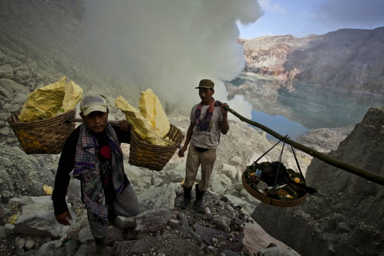 Miners carry a goats head for burial in the crater as part of an annual offering ceremony on the Ijen volcano on December 17, 2013 in Yogyakarta, Indonesia. The ritual is performed by the sulfur miners of Mount Ijen who slaughter a goat and then bury the head in the crater of mount Ijenn. The sacrifice is performed to ward off potential disasters for the next year. The Ijen crater rises to 2,386m, with a depth of over 175m, making it one of the world's largest craters. Sulphur mining is a major industry in the region, made possible by an active vent at the edge of a lake, but the work is not without risks as the acidity of the water in the crater is high enough to dissolve clothing and cause breathing problems. (Ulet Ifansasti/Getty Images)