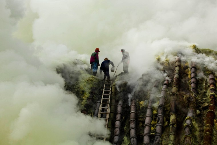 A sulfur miner carries a goat head in a white bag as he climbs to bury the head in the crater as part of an annual offering ceremony on the Ijen volcano on December 17, 2013 in Yogyakarta, Indonesia. The ritual is performed by the sulfur miners of Mount Ijen who slaughter a goat and then bury the head in the crater of mount Ijenn. The sacrifice is performed to ward off potential disasters for the next year. The Ijen crater rises to 2,386m, with a depth of over 175m, making it one of the world's largest craters. Sulphur mining is a major industry in the region, made possible by an active vent at the edge of a lake, but the work is not without risks as the acidity of the water in the crater is high enough to dissolve clothing and cause breathing problems. (Ulet Ifansasti/Getty Images)