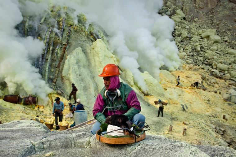 A miner sits beside a goat head as he prepares for its burial in the crater as part of an annual offering ceremony on the Ijen volcano on December 17, 2013 in Yogyakarta, Indonesia. The ritual is performed by the sulfur miners of Mount Ijen who slaughter a goat and then bury the head in the crater of mount Ijenn. The sacrifice is performed to ward off potential disasters for the next year. The Ijen crater rises to 2,386m, with a depth of over 175m, making it one of the world's largest craters. Sulphur mining is a major industry in the region, made possible by an active vent at the edge of a lake, but the work is not without risks as the acidity of the water in the crater is high enough to dissolve clothing and cause breathing problems. (Ulet Ifansasti/Getty Images)