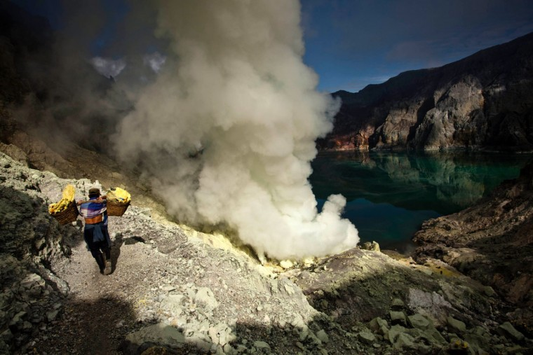 A miner carries sulfur during an annual offering ceremony on the Ijen volcano on December 17, 2013 in Yogyakarta, Indonesia. The ritual is performed by the sulfur miners of Mount Ijen who slaughter a goat and then bury the head in the crater of mount Ijenn. The sacrifice is performed to ward off potential disasters for the next year. The Ijen crater rises to 2,386m, with a depth of over 175m, making it one of the world's largest craters. Sulfur mining is a major industry in the region, made possible by an active vent at the edge of a lake, but the work is not without risks as the acidity of the water in the crater is high enough to dissolve clothing and cause breathing problems. (Ulet Ifansasti/Getty Images)