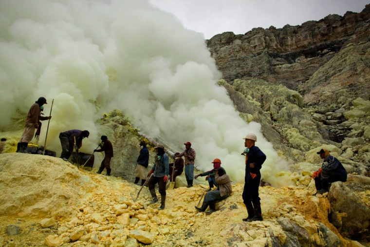 Miners uses poles to extract sulfur from pipes at the flow crater during an annual offering ceremony on the Ijen volcano on December 17, 2013 in Yogyakarta, Indonesia. The ritual is performed by the sulfur miners of Mount Ijen who slaughter a goat and then bury the head in the crater of mount Ijenn. The sacrifice is performed to ward off potential disasters for the next year. The Ijen crater rises to 2,386m, with a depth of over 175m, making it one of the world's largest craters. Sulfur mining is a major industry in the region, made possible by an active vent at the edge of a lake, but the work is not without risks as the acidity of the water in the crater is high enough to dissolve clothing and cause breathing problems. (Ulet Ifansasti/Getty Images)