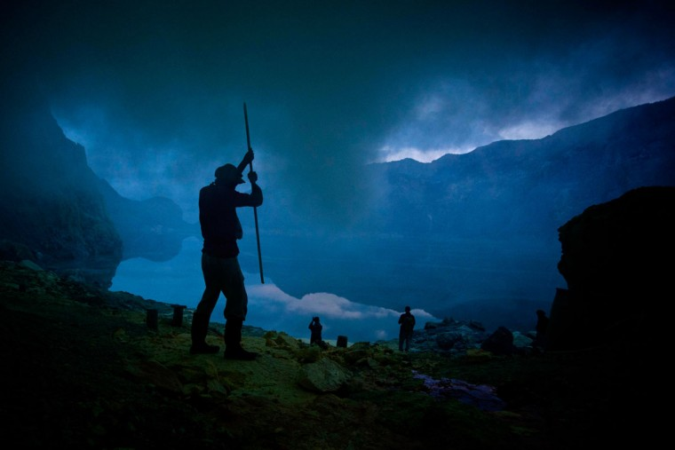 A miner uses a pole to extract sulfur from a pipe at the flow crater during an annual offering ceremony on the Ijen volcano on December 17, 2013 in Yogyakarta, Indonesia. The ritual is performed by the sulfur miners of Mount Ijen who slaughter a goat and then bury the head in the crater of mount Ijenn. The sacrifice is performed to ward off potential disasters for the next year. The Ijen crater rises to 2,386m, with a depth of over 175m, making it one of the world's largest craters. Sulphur mining is a major industry in the region, made possible by an active vent at the edge of a lake, but the work is not without risks as the acidity of the water in the crater is high enough to dissolve clothing and cause breathing problems. (Ulet Ifansasti/Getty Images)