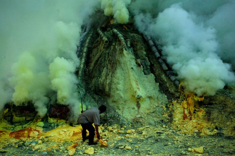 A miner extracts sulfur from pipe at the flow crater during an annual offering ceremony on the Ijen volcano on December 17, 2013 in Yogyakarta, Indonesia. The ritual is performed by the sulfur miners of Mount Ijen who slaughter a goat and then bury the head in the crater of mount Ijenn. The sacrifice is performed to ward off potential disasters for the next year. The Ijen crater rises to 2,386m, with a depth of over 175m, making it one of the world's largest craters. Sulphur mining is a major industry in the region, made possible by an active vent at the edge of a lake, but the work is not without risks as the acidity of the water in the crater is high enough to dissolve clothing and cause breathing problems. (Ulet Ifansasti/Getty Images)