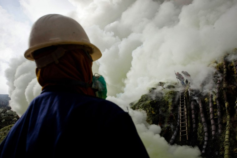 A sulfur miner looks at the crater as they prepare to bury the head in the crater as part of an annual offering ceremony on the Ijen volcano on December 17, 2013 in Yogyakarta, Indonesia. The ritual is performed by the sulfur miners of Mount Ijen who slaughter a goat and then bury the head in the crater of mount Ijenn. The sacrifice is performed to ward off potential disasters for the next year. The Ijen crater rises to 2,386m, with a depth of over 175m, making it one of the world's largest craters. Sulfur mining is a major industry in the region, made possible by an active vent at the edge of a lake, but the work is not without risks as the acidity of the water in the crater is high enough to dissolve clothing and cause breathing problems. (Ulet Ifansasti/Getty Images)