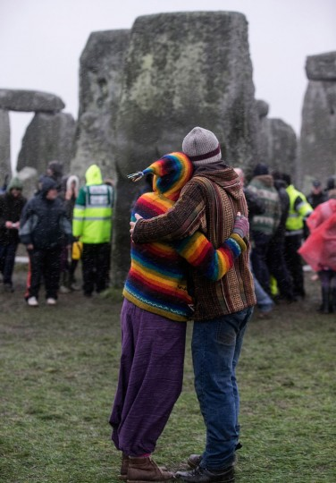 A couple embrace as druids, pagans and revellers gather in the centre of Stonehenge, hoping to see the sun rise, as they take part in a winter solstice ceremony at Stonehenge on December 21, 2013 in Wiltshire, England. Despite the rain and wind, a large crowd gathered at the famous historic stone circle to celebrate the sunrise closest to the Winter Solstice, the shortest day of the year - an event claimed to be more important in the pagan calendar than the summer solstice, because it marks the 're-birth' of the Sun for the New Year.