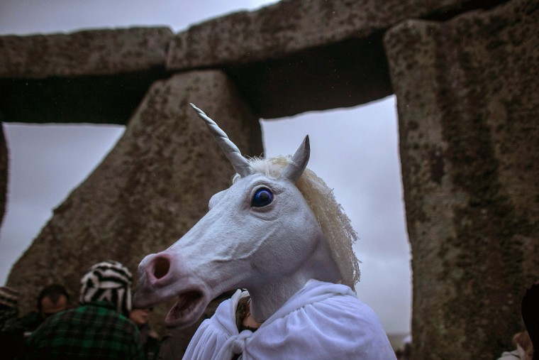 A woman wearing a unicorn mask watches as druids, pagans and revellers gather, hoping to see the sun rise as they take part in a winter solstice ceremony at Stonehenge on December 21, 2013 in Wiltshire, England. Despite the rain and wind, a large crowd gathered at the famous historic stone circle to celebrate the sunrise closest to the Winter Solstice, the shortest day of the year - an event claimed to be more important in the pagan calendar than the summer solstice, because it marks the 're-birth' of the Sun for the New Year.