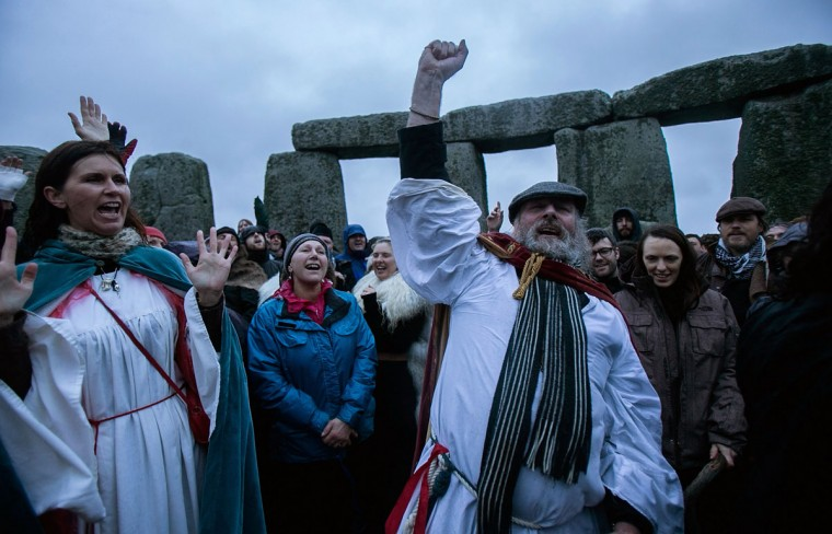 Rollo Maughfling, Archdruid of Stonehenge & Britain, (R) conducts a ceremony as druids, pagans and revellers gather, hoping to see the sun rise as they take part in a winter solstice ceremony at Stonehenge on December 21, 2013 in Wiltshire, England. Despite the rain and wind, a large crowd gathered at the famous historic stone circle to celebrate the sunrise closest to the Winter Solstice, the shortest day of the year - an event claimed to be more important in the pagan calendar than the summer solstice, because it marks the 're-birth' of the Sun for the New Year.