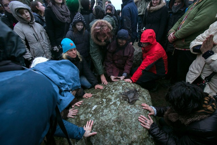 People touch a stone inside Stonehenge as druids, pagans and revellers gather in the centre of Stonehenge, hoping to see the sun rise, as they take part in a winter solstice ceremony at Stonehenge on December 21, 2013 in Wiltshire, England. Despite the rain and wind, a large crowd gathered at the famous historic stone circle to celebrate the sunrise closest to the Winter Solstice, the shortest day of the year - an event claimed to be more important in the pagan calendar than the summer solstice, because it marks the 're-birth' of the Sun for the New Year.