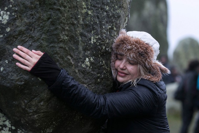 A woman hugs the stones as druids, pagans and revellers gather, hoping to see the sun rise as they take part in a winter solstice ceremony at Stonehenge on December 21, 2013 in Wiltshire, England. Despite the rain and wind, a large crowd gathered at the famous historic stone circle to celebrate the sunrise closest to the Winter Solstice, the shortest day of the year - an event claimed to be more important in the pagan calendar than the summer solstice, because it marks the 're-birth' of the Sun for the New Year.