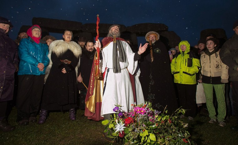 Rollo Maughfling, Archdruid of Stonehenge & Britain, (centre) conducts a ceremony as druids, pagans and revellers gather, hoping to see the sun rise as they take part in a winter solstice ceremony at Stonehenge on December 21, 2013 in Wiltshire, England. Despite the rain and wind, a large crowd gathered at the famous historic stone circle to celebrate the sunrise closest to the Winter Solstice, the shortest day of the year - an event claimed to be more important in the pagan calendar than the summer solstice, because it marks the 're-birth' of the Sun for the New Year.